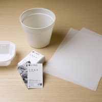 Business cards, plastic folders and food containers made from limestone are displayed at TBM Co.'s headquarters in Tokyo. | BLOOMBERG