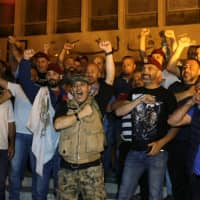 Retired soldiers take part in a protest over proposed cuts to the cost of military pensions and benefits, in front of the central bank in Beirut Sunday. | REUTERS