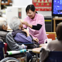 A care worker from Indonesia tends to elderly people at a facility for the aged in the city of Tenri, Nara Prefecture, in March 2017. | KYODO