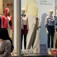 People walk past a Uniqlo store in Tokyo. Japan's core consumer prices rose 0.9 percent in April from a year earlier due to robust demand for overseas package tours and rising energy prices, according to government data released Friday. | BLOOMBERG