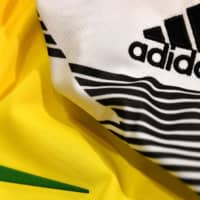 The logos of sports wear manufacturers Nike and Adidas for the FIFA 2018 World Cup football tournament are seen last year in Paris. Adidas, Nike and PUMA on Tuesday urged U.S. President Donald Trump to prevent the shoe industry from falling victim to the trade war with China, saying new tariffs could be 'catastrophic.' | AFP-JIJI