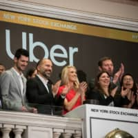 Uber CEO Dara Khosrowshahi (center, dark jacket) rings the opening bell during the company's IPO at the New York Stock Exchange on Friday. | BLOOMBERG