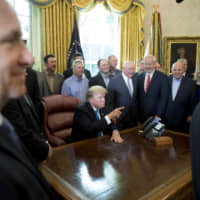 President Donald Trump, accompanied by Agriculture Secretary Sonny Perdue *left), gestures as he answers a question from a reporter during a meeting to support America's farmers and ranchers in the Roosevelt Room of the White House Thursday in Washington. | AP