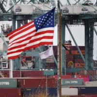 Chinese shipping containers are stored beside a U.S. flag after they were unloaded at the Port of Los Angeles in Long Beach, California, on Tuesday.   AFP-JIJI