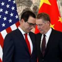 U.S. Treasury Secretary Steven Mnuchin (left) huddles with Trade Representative Robert Lighthizer as they arrive for a group photo session after their meeting with Chinese Vice Premier Liu He, at the Diaoyutai State Guesthouse in Beijing Wednesday. | ANDY WONG / POOL / VIA REUTERS