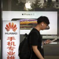 A man looks at his smartphone as he walks past an electronics shop advertising phones from Huawei and Apple in Beijing on Friday. | AP