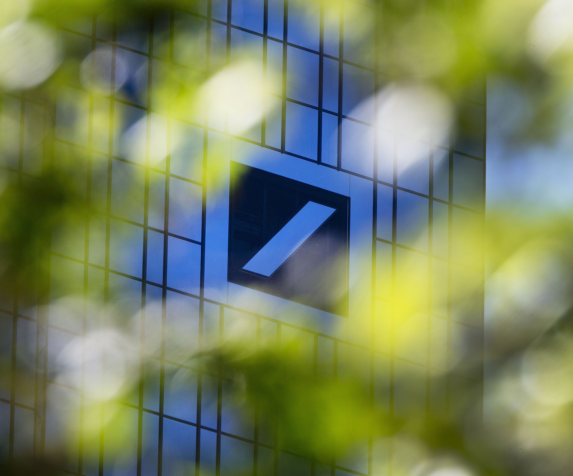 The headquarters of Deutsche Bank is seen through green leaves in Frankfurt, Germany, Tuesday. U.S. President Donald Trump has gone to court to fight an attempt by the House to obtain his business records. On Monday the president and three of his children filed suit in federal court in New York against Deutsche Bank and Capital One. | AP