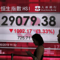 People walk past a bank's electronic display showing the share index at the Hong Kong Stock Exchange on Monday. Shares tumbled in Asia excluding Japan early Monday after President Donald Trump threatened in a tweet to impose more tariffs on China, spooking investors who had been expecting good news on trade. | AP