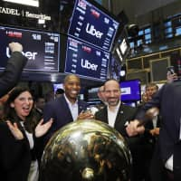 Uber board member Ryan Graves (right) rings a ceremonial bell as the company's stock opens for trading during its initial public offering at the New York Stock Exchange Friday. Stacey Cunningham (second from left), president of the NYSE, Tony West (center), Uber's Chief Legal Officer, and CEO Dara Khosrowshahi (second from right) applaud. A fare war between Uber and Lyft has led to billions of dollars in losses for both ride-hailing companies as they fight for passengers and drivers. | AP