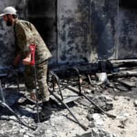 A wounded fighter loyal to Libya's U.N.-backed government (GNA) walks in front of a house burned during clashes with troops loyal to Khalifa Hifter in the Wadi Rabiya neighborhood on the outskirts of Tripoli Tuesday. | REUTERS