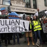 Protestors demonstrate at the entrance of Westminster Magistrates Court in London Thursday. WikiLeaks founder Julian Assange is facing a court hearing over a U.S. request to extradite him for allegedly conspiring to hack a Pentagon computer. | AP