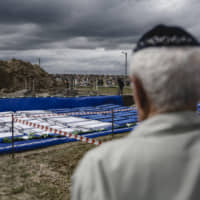 A man looks at coffins before burying the remains of Holocaust victims at a cemetery just outside Brest, Belarus, Wednesday. Remains of more than 1,000 Holocaust victims were laid to rest on Wednesday in the Belarusian city on the border with Poland after a mass grave was discovered on a building site earlier this year. | ULADZ HRYDZIN, RADIO FREE EUROPE / RADIO LIBERTY / VIA AP