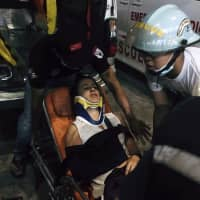 Myanmar rescue members help an injured passenger in Yangon International airport Wednesda. A plane operated by Biman Bangladesh Airlines skidded off the runway while landing Wednesday evening at Myanmar's Yangon International Airport. | AP