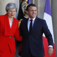 French President Emmanuel Macron greets British Prime Minister Theresa May at the Elysee Palace in Paris Wednesday. | AP