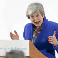 Theresa May, U.K. prime minister, gestures while delivering a speech setting out a new proposal for her Brexit deal in London on Tuesday. She is considering tighter customs ties with the European Union to try to win over Labour lawmakers, but the strategy risks angering Brexiteers in her government. | BLOOMBERG