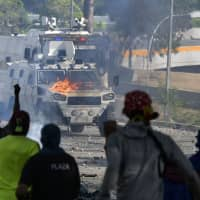 Anti-government protesters clash with security forces during the commemoration of May Day on Wednesday after a day of violent clashes on the streets of the capital spurred by Venezuela's opposition leader Juan Guaido's call on the military to rise up against President Nicolas Maduro. | AFP-JIJI