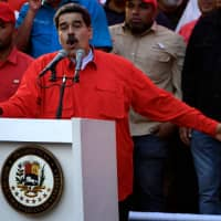 Venezuelan President Nicolas Maduro speaks during a May Day rally in Caracas Wednesday. Opposition supporters demonstrated for a second consecutive day in support of their country's self-proclaimed leader, Juan Guaido, as he bids to overthrow Maduro. | AFP-JIJI
