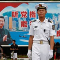 A Chinese People's Liberation Army Navy seaman stands in front of a backdrop featuring President Xi Jinping at a naval base in Hong Kong in 2017. | REUTERS