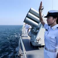 A Chinese sailor waves farewell to Russian vessels as a Chinese-Russian joint naval drill concludes in Zhanjiang, in China's Guangdong province, in September 2016. | REUTERS