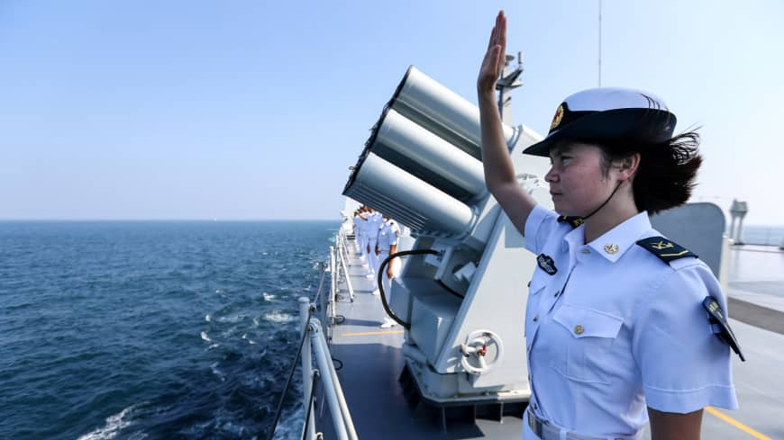 A Chinese sailor waves farewell to Russian vessels as a Chinese-Russian joint naval drill concludes in Zhanjiang, in China