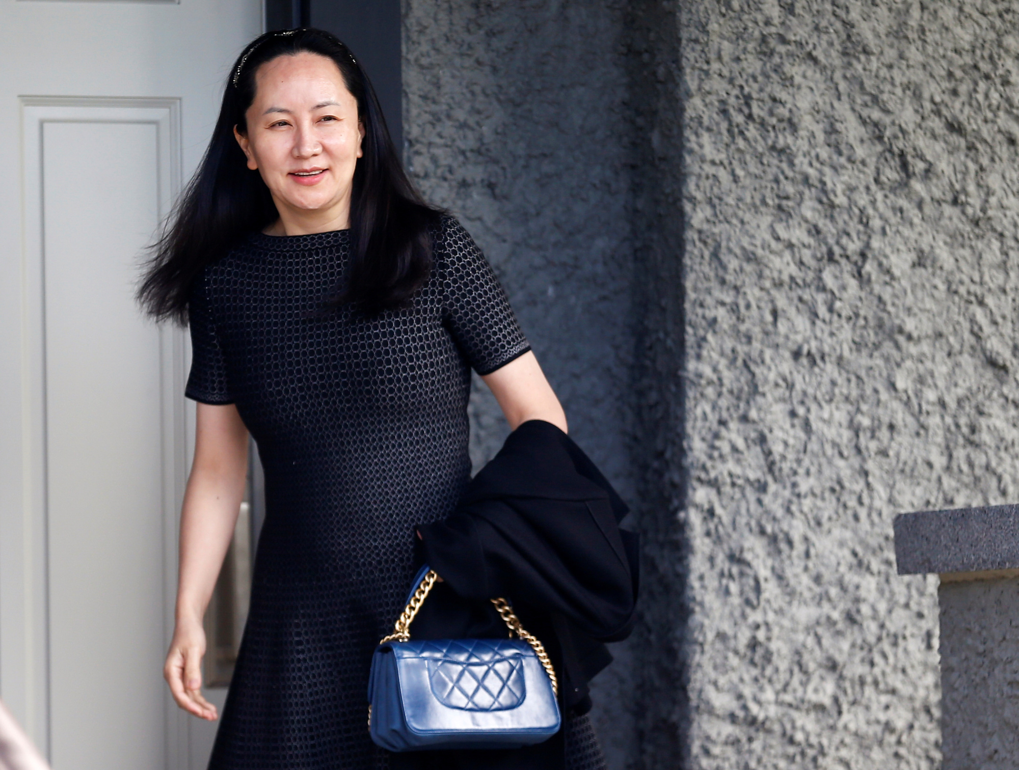Huawei Technologies Co. executive Meng Wanzhou leaves her family home in Vancouver, British Columbia, on Wednesday. | REUTERS