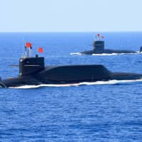 Two Chinese People's Liberation Army Navy nuclear-powered Type 094A Jin-class ballistic missile submarines are seen during a military parade in the South China Sea on April 12, 2018. | REUTERS