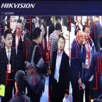Visitors are tracked by facial recognition technology from state-owned surveillance equipment manufacturer Hikvision at the Security China 2018 expo in Beijing in October 2018. | AP
