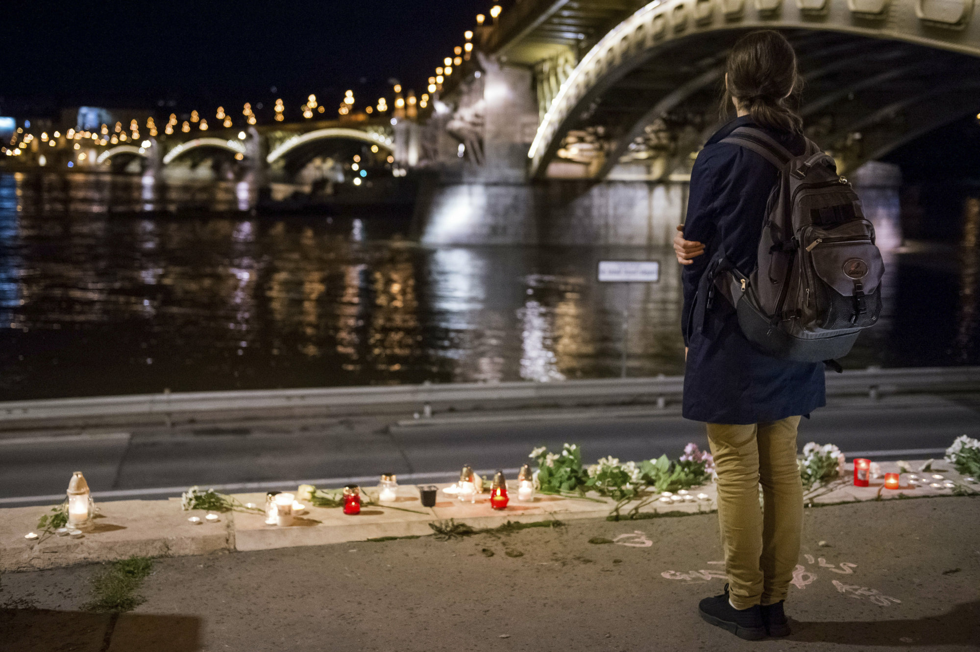 A woman stands by flowers and candles placed on the riverbank to pay tribute to the victims of the capsized boat at Margaret Bridge, in Budapest Thursday. Rescue crews were preparing to raise a sightseeing boat from the bottom of the Danube River Thursday as search teams scoured the waters for 21 people missing after the vessel, packed with South Korean tourists, collided with a larger cruise ship and sank. | AP
