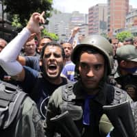 An anti-government protester gestures next to Venezuelan National Guard members who joined a march supporting opposition leader Juan Guaido in Caracas Tuesday. | REUTERS