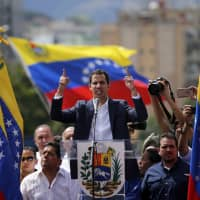 Juan Guaido, head of Venezuela's opposition-run congress, declares himself interim president of the nation until elections can be held, during a rally demanding President Nicolas Maduro's resignation, in Caracas in January. | AP