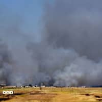Smoke billows above buildings in the town of Kafr Nabuda in the north of the Syrian Hama province during reported airstrikes by Syrian regime forces on Sunday. | AFP-JIJI