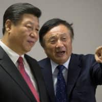 Chinese President Xi Jinping pauses as he is shown around the offices of Huawei Technologies Co. by Ren Zhengfei, president of Huawei, in London in 2015. | REUTERS