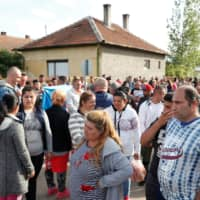 Roma people gather on the outskirts of the town to commemorate the killings of Roma people by right-wing militants in 2009, in Torokszentmiklos, Hungary, Tuesday.