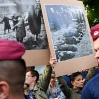 Anti-fascist sympathizers hold historical photos of the 20th century as new Hungarian far-right group, the Our Homeland Movement and their sympathizers, members of the National Legio, protest during a demonstration against the Roma community in Torokszentmiklos, about 130 km east of Budapest, on Tuesday. | AFP-JIJI
