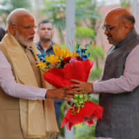 Indian Prime Minister Narendra Modi receives a bouquet from Bharatiya Janata Party President Amit Shah upon his arrival at a ceremony in New Delhi on Tuesday. | REUTERS
