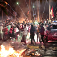 Firecrackers explode near supporters of presidential candidate Prabowo Subianto during clashes with the police in Jakarta on Wednesday. Indonesian President Joko 'Jokowi' Widodo said authorities had the volatile situation under control after six people died Wednesday in riots. | AP