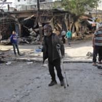 A Syrian man whose shop was destroyed in a regime aerial bombardment the previous day walks around the area on May 15 in Jisr al-Shughur in Syria's jihadist-held Idlib province. | AFP-JIJI