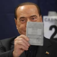Former Italian Prime Minister Silvio Berlusconi holds up his ballot for the European Parliament elections at a polling station in Milan, Italy, Sunday.   AP