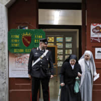 A Carabiniere (Italian paramilitary police) officer looks at nuns as they leave a polling station after voting for the European Parliament elections, in Rome Sunday.   AP