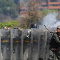 A member of the National Guard throws an object toward opposition supporters during a rally against the government of Venezuelan President Nicolas Maduro and to commemorate May Day in Caracas Wednesday. | REUTERS