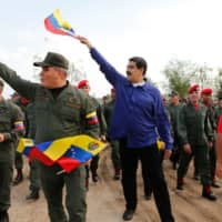 Venezuelan President Nicolas Maduro and Defense Minister Vladimir Padrino (left) wave the country's national flag during a 'march of loyalty' with the Superior Staff of the Venezuela's Bolivarian National Armed Forces and other military personnel in Aragua state on  Friday. | AFP-JIJI