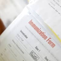 A camper's immunization form and physician's stamp is seen at the Rosmarins Day Camp and Cottages office in Monroe, New York, May 20. | REUTERS
