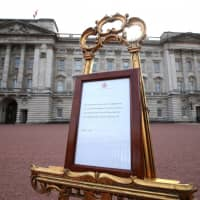 A notice placed on an easel in the forecourt of Buckingham Palace announces the birth of a baby boy to Britain's Prince Harry and Meghan, Duchess of Sussex, in London Monday. | YUI MOK / POOL / VIA REUTERS