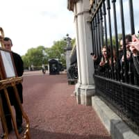 People take pictures as royal footmen place an easel in the forecourt of Buckingham Palace to formally announce the birth of a baby boy to Prince Harry and Meghan, Duchess of Sussex, in London, on Monday. | REUTERS