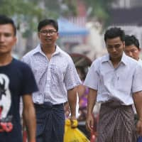Reuters reporters Wa Lone (center, left) and Kyaw Soe Oo (center, right) walk free outside Insein Prison after receiving a presidential pardon in Yangon on Tuesday. | REUTERS