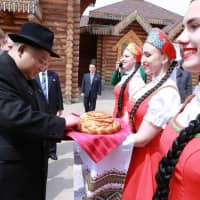 North Korean leader Kim Jong Un receives a welcome by women wearing traditional clothing with bread and salt at a restaurant in Vladivostok on April 26. | KCNA / VIA KNS / VIA AFP-JIJI