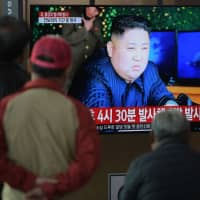 People watch a television news program showing a picture of North Korean leader Kim Jong Un, at a railway station in Seoul on Thursday. | AFP-JIJI