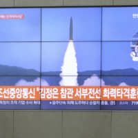A man watches TV screens showing a photo of a North Korean missile and South Korean Foreign Minister Kang Kyung-wha meeting with U.S. Special Representative for North Korea Stephen Biegun during news programs at the Yonhap news agency building in Seoul on Friday. | AP