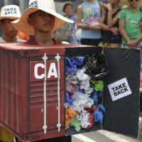 Filipino environmental activists wear a mock container vans filled with garbage to symbolize the 50 containers of waste that were shipped from Canada to the Philippines two years ago as they hold a protest outside the Canadian Embassy in the financial district of Makati, south of Manila, on May 7. | AP