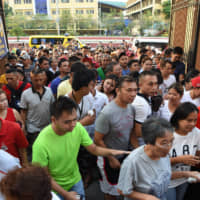 Voters rush inside as the gate opens at a polling precinct in Manila on Monday for a midterm poll. The vote was expected to strengthen President Rodrigo Duterte's grip on power, opening the way for him to deliver on pledges to restore the death penalty and rewrite the constitution. | AFP-JIJI
